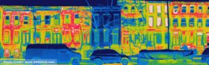 A thermal image of a row of townhouses. All houses glow green, yellow and red indicating heat being lost from the building, except one house in the middle that is dark blue, indicating very little heat loss.